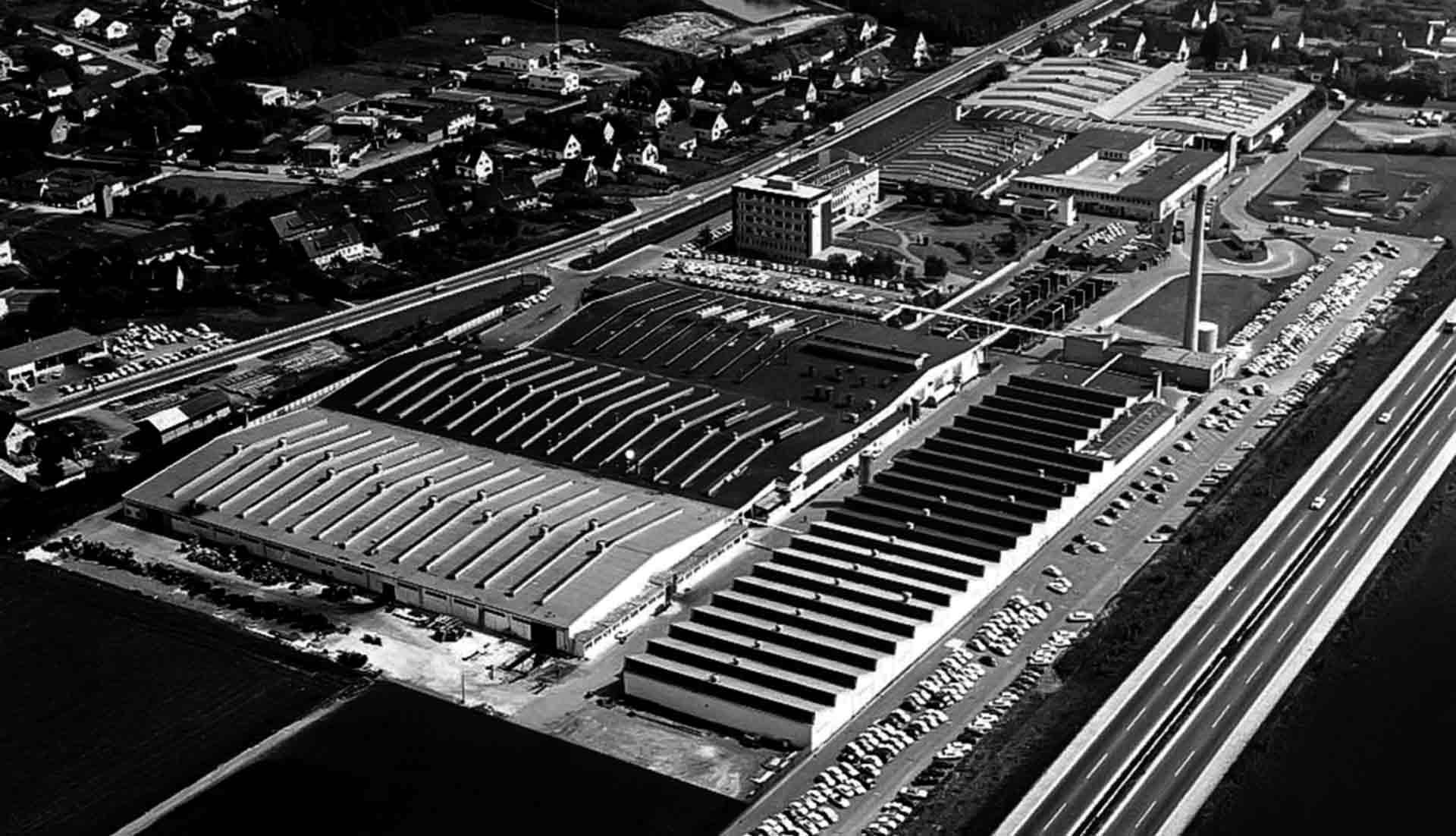 Bis 1970 ist das Werk Lohmar beeindruckend gewachsen: Die Verwaltung ist fünfgeschossig ausgebaut, vorne rechts die Shedhalle mit Lehrwerkstatt, dahinter das Heizkraftwerk mit Schornstein.